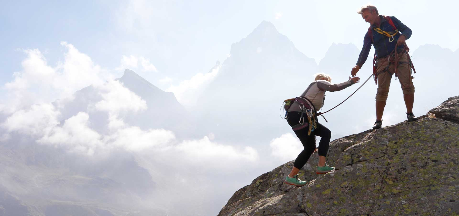 A man and a Women climbing a mountain with ropes.