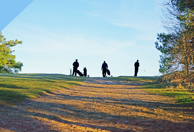 Three people Playing golf on a hill