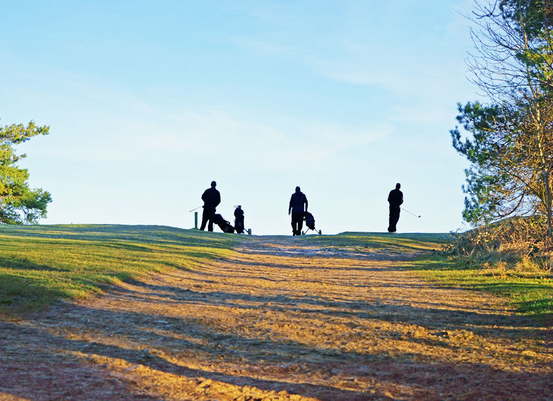 Three people playing Golf on the top of a hill.